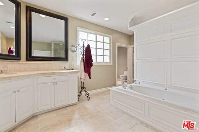 This bright master bathroom has beige walls accented with white elements of the vanity cabinets and the white wooden structure housing the bathtub. There is a nice wrought iron standing coat rug beside the vanity repurposed for the towels and robes.
