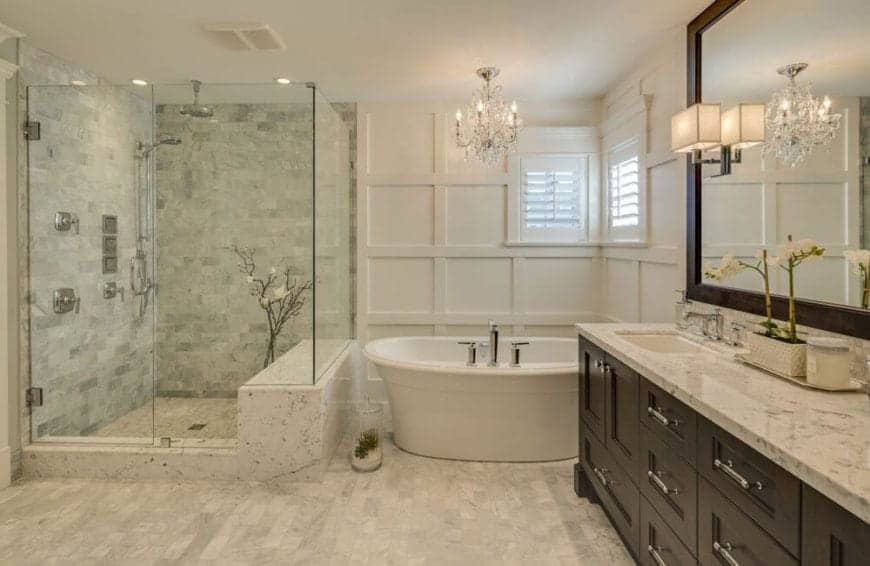 The big shower area is enclosed with glass beside the freestanding bathtub placed in a corner of white wooden walls with two shuttered windows and a small crystal chandelier on top for a touch of elegance.