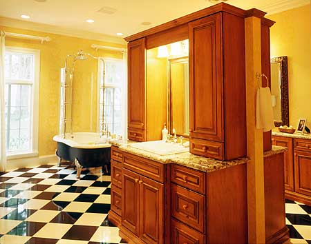 The black and white checkered flooring of this master bathroom is a nice contrast to the yellow walls and the wooden structure of the vanity that has two sinks back-to-back with each other. The freestanding bathtub fits in with the aesthetic of the floor.