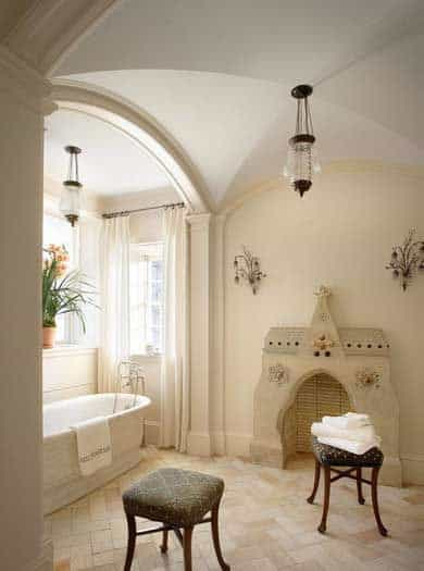 This bathroom has a groin ceiling with a pendant light in the middle and a fireplace embedded into the beige wall near the white freestanding tub illuminated by a window by its head.