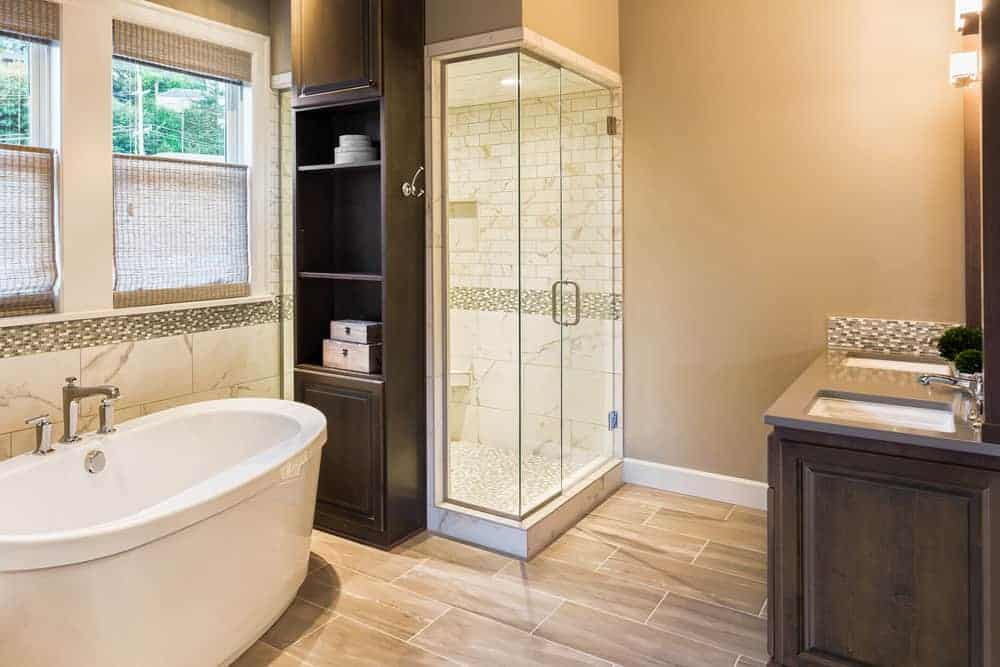 This lovely bathroom has a freestanding bathtub by the window and a small wooden cabinet by its head near the walk-in shower across from the two-sink vanity area.