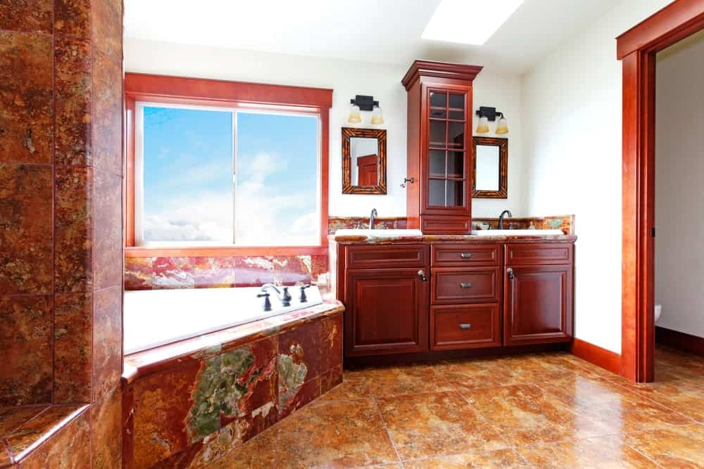 The redwood hue of the wooden cabinets and drawers of the two-sink vanity area matches with the reddish rust hue of the marble flooring that extends to the bathtub housing.