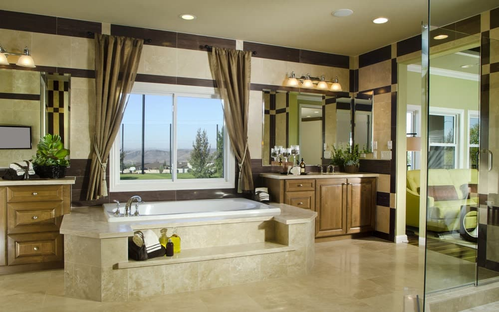 The marble enclosed bathtub that blends with the marble flooring is flanked by the two vanity area with their own sinks and large wall-mounted mirrors topped with wall lamps with yellow light.