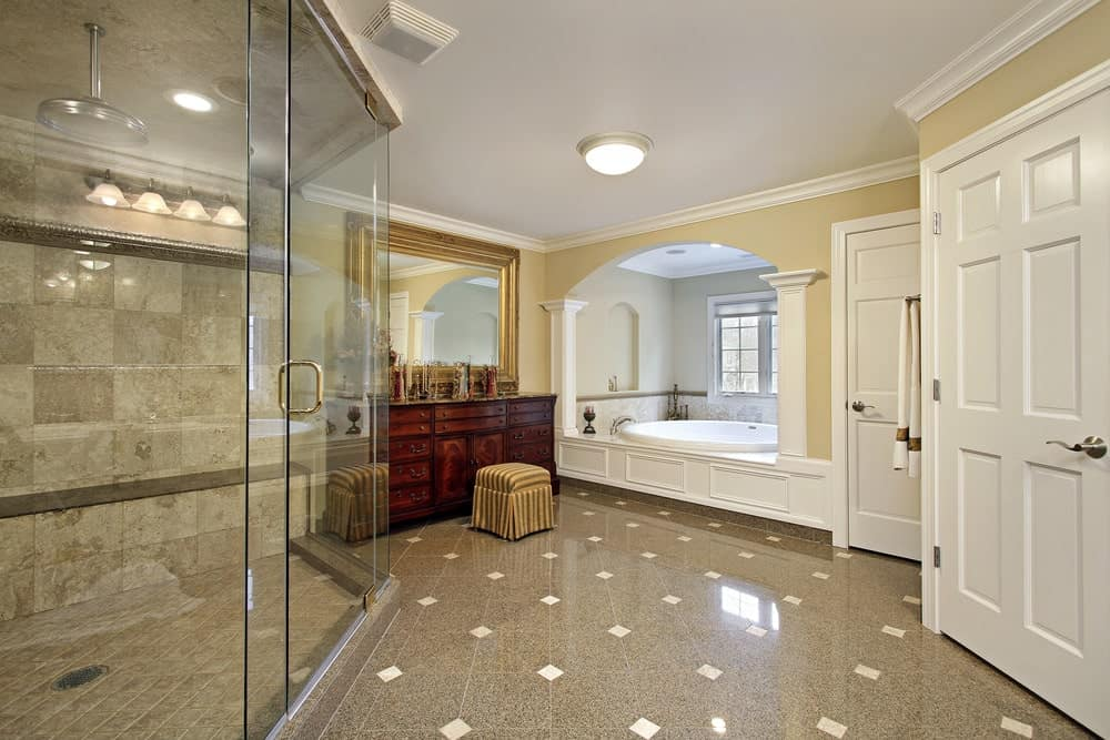 The gray tiles of the flooring is dotted with diamond patterns that provide a nice complex contrast to the solid matte beige walls and white ceiling that blends with the white doors and housing of the bathtub flanked with white columns embedded into the walls.