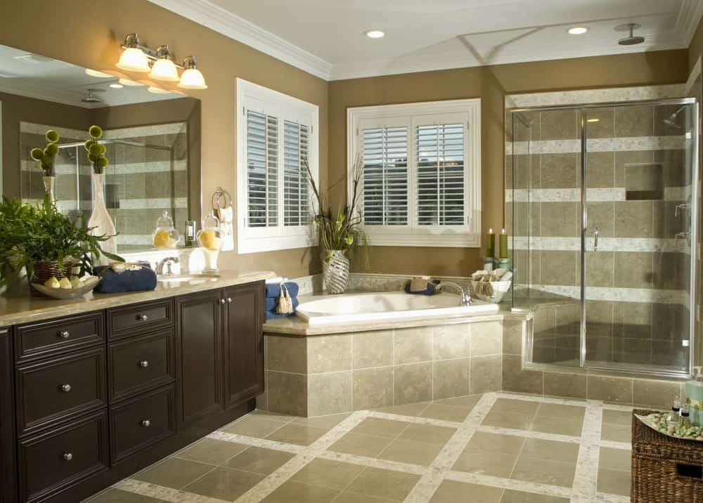 The tiled walls and flooring of the shower area have a pattern that is reflected by the flooring of the rest of the bathroom by the vanity beside the bathtub that is placed in a corner with two shuttered windows.