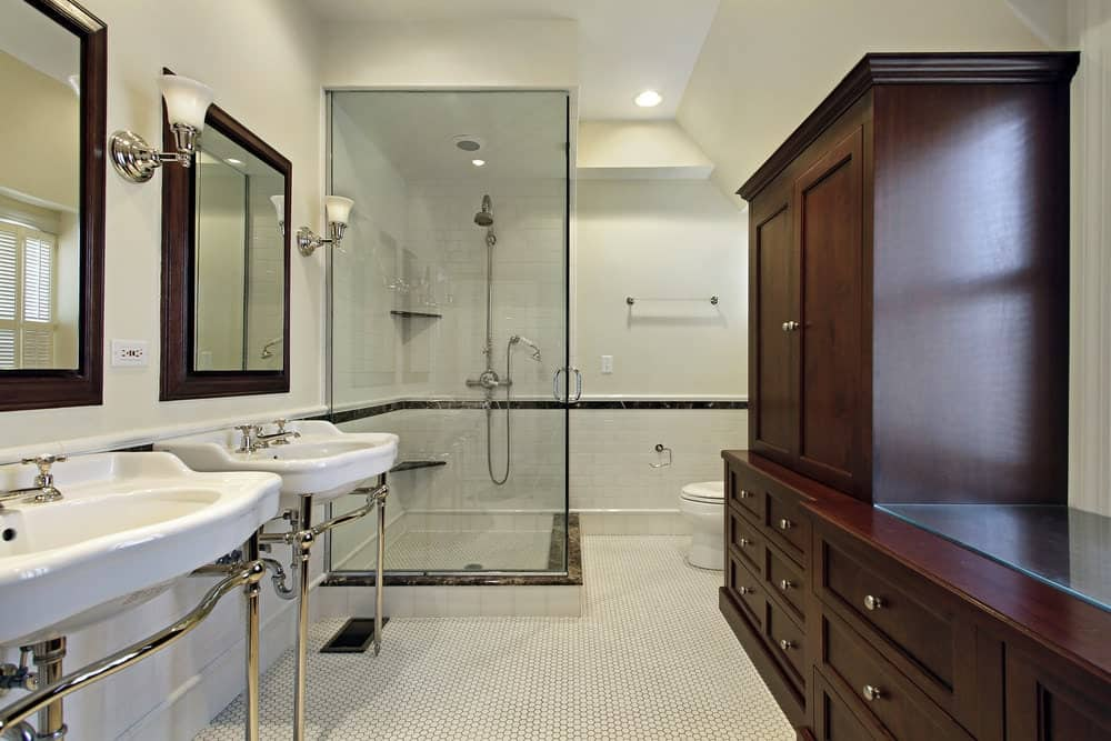 The pair of white porcelain sinks are supported by silver stands and topped with mirrors framed in wood that pairs well with the wooden structure with cabinets and drawers beside the white toilet.