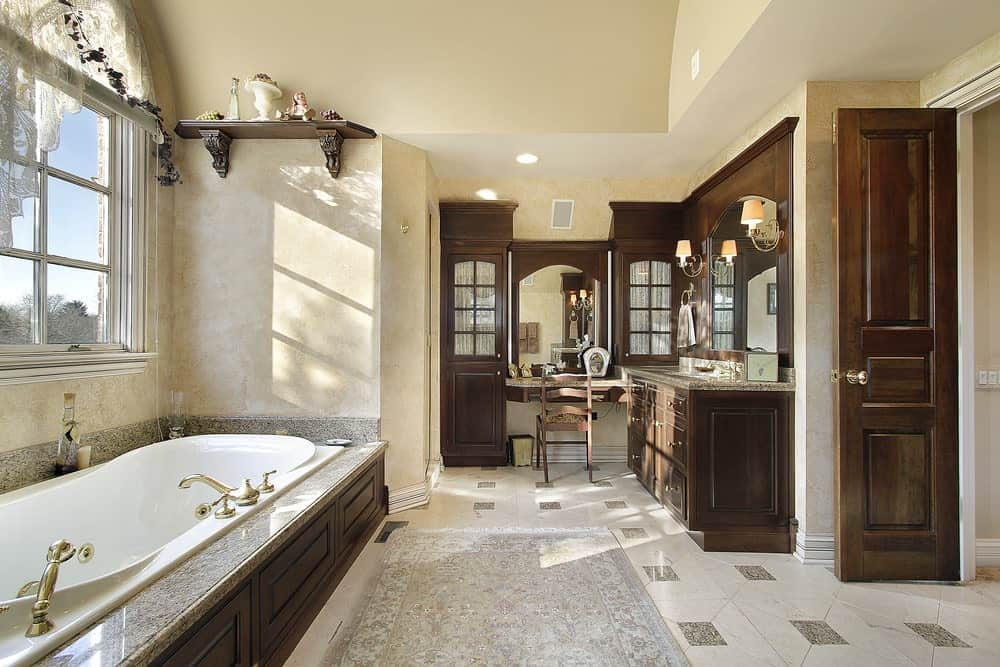 The white bathtub by the window has a grainy gray countertop and backsplash that matches with the patterns of the floor tiles that is topped with a white patterned area rug and contrasted by the wooden vanity.