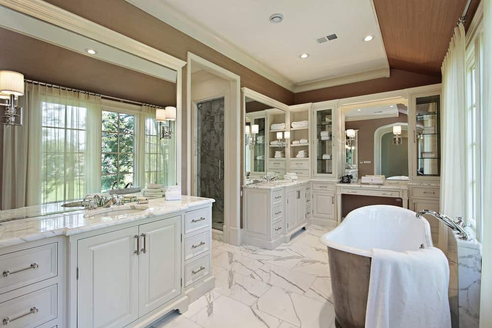 The wooden ceiling has a white tray center that matches with the white marble flooring and the white cabinets and drawers of the two vanity areas with their own sinks and mirrors with wall-mounted lamps on them.