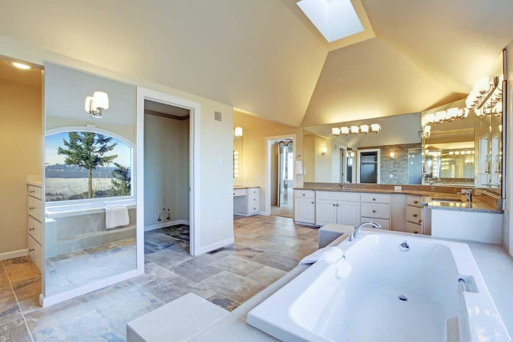 The wide and spacious quality of this marble-floored primary bathroom is augmented by the large mirrors mounted on the walls above the L-shaped vanity area and the wall across from the bathtub by the window.