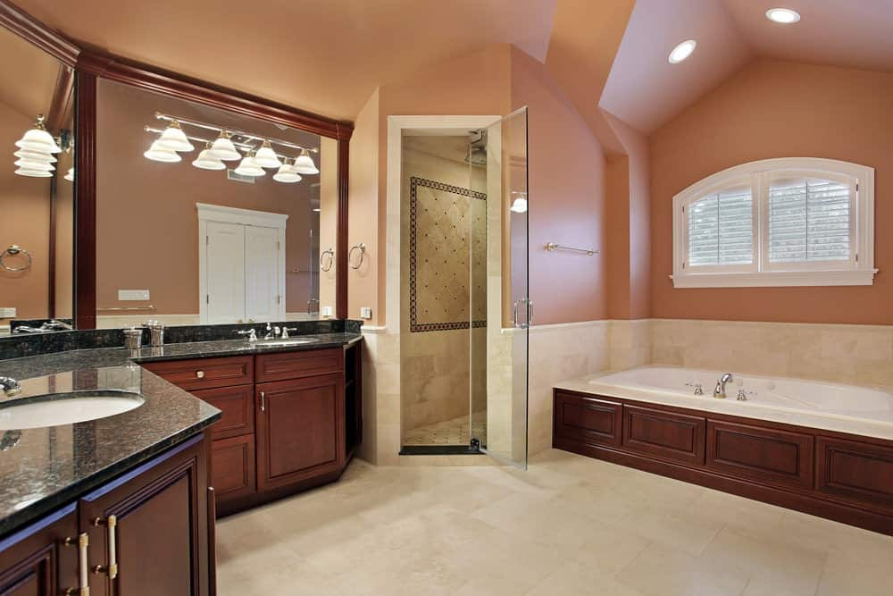 This charming pink-walled bathroom has an L-shaped vanity area with black countertops housing two white sinks with wood-framed mirrors above across from the bathtub that is housed in the same wooden design as the vanity.