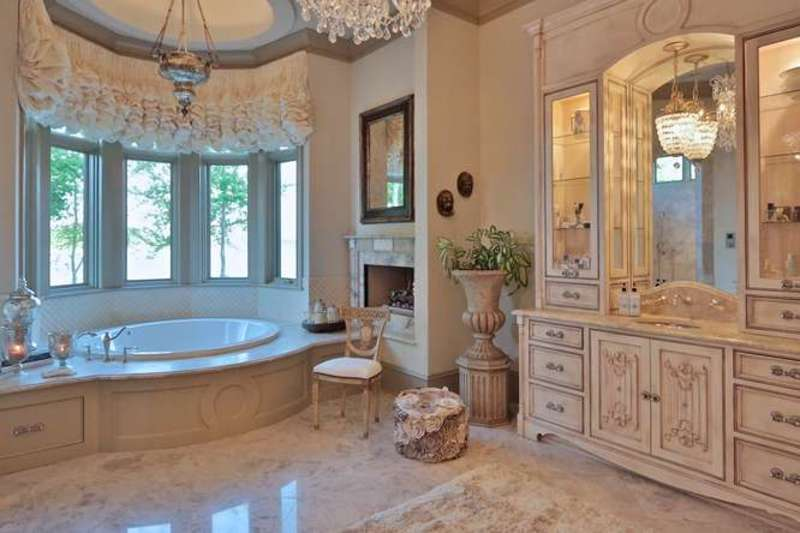 This elegant master bathroom is fit for royalty with its bathtub in a round alcove with a row of windows and even a small fireplace. This is paired with a large wooden structure that houses the vanity with elegant cabinets and drawers.