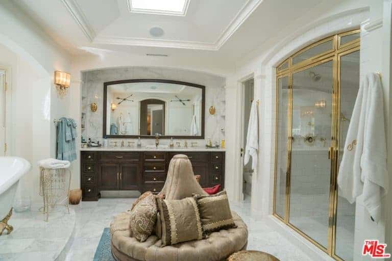 This spacious bathroom has a white tray ceiling paired with a white marble flooring with a leader cushioned sitting area in the middle between the white freestanding bathtub and the gold-trimmed shower area.
