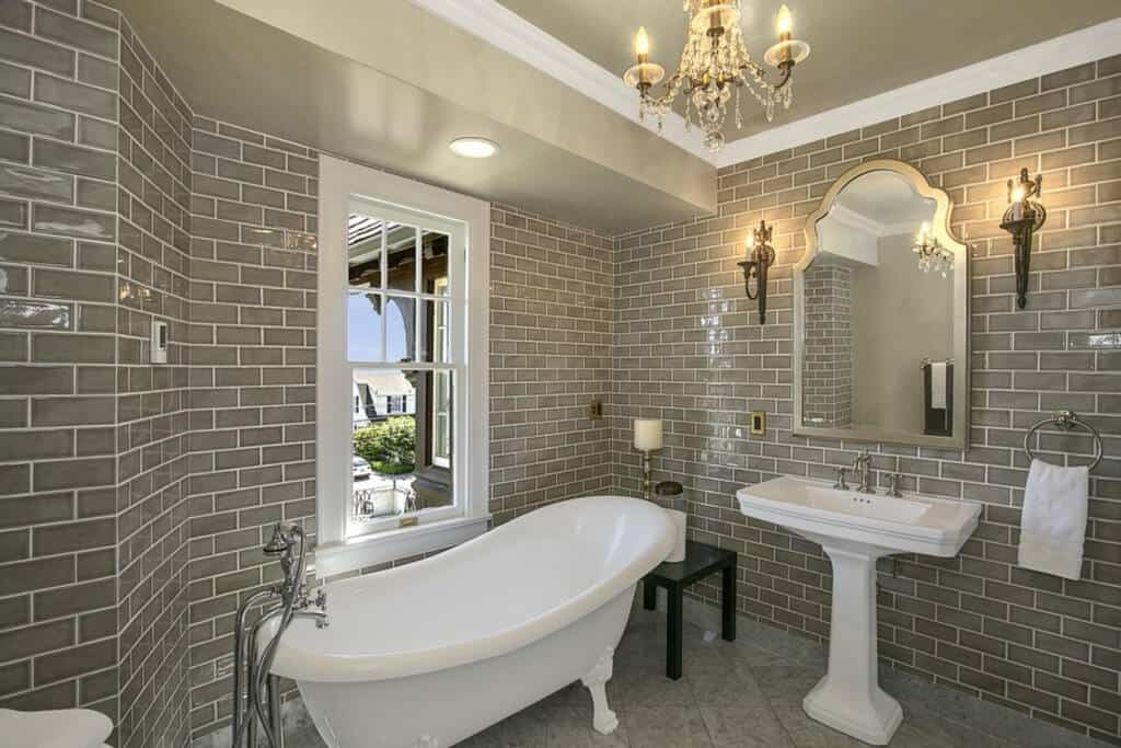 The white freestanding bathtub and white sink with porcelain stand stands out against the gray tiles of the wall that makes it look like a dungeon-wall. This is augmented by a crystal chandelier and wall lamps flanking the vanity mirror.