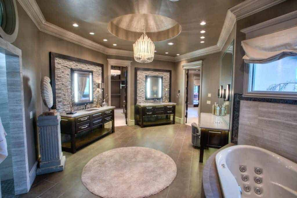 This is an elegant and spacious bathroom with gray floor tiles topped with a circular area rug beneath the circular tray of the ceiling with an elegant crystal chandelier in the middle.