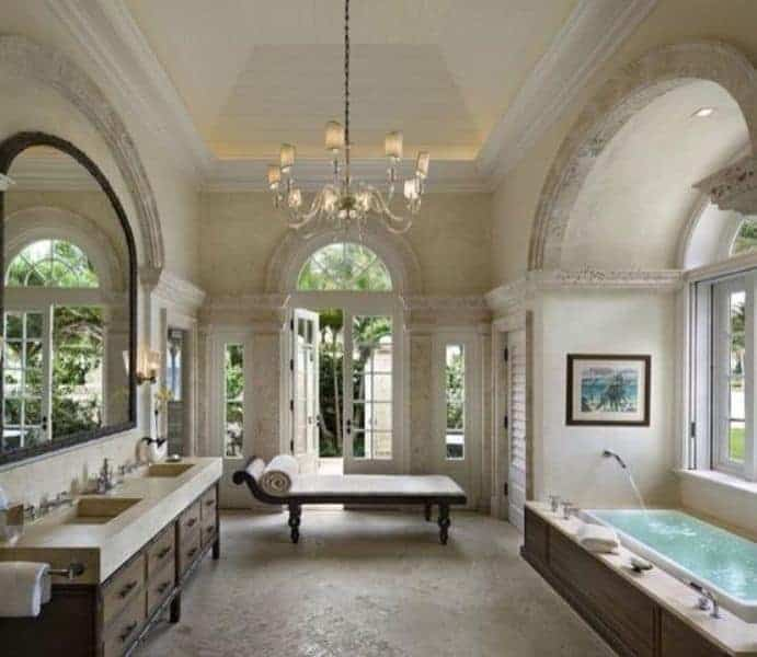 The high and white cove ceiling has a majestic white chandelier hanging in between the bathtub and the vanity area with an immense wall-mounted mirror.