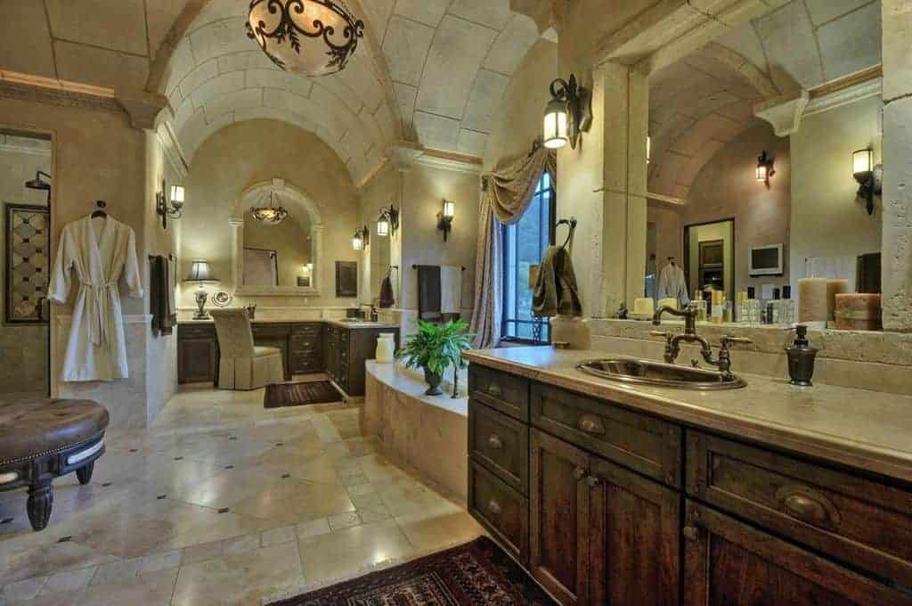 This is a grand bathroom that oozes elegance with its high groin ceiling with a pendant light over the white marble flooring contrasted by the wooden drawers and cabinets of the vanity beside the bathtub enclosed in marble.