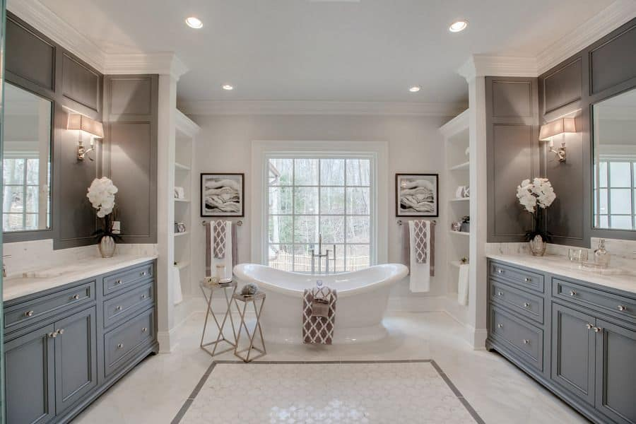 The freestanding bathtub stands in the middle of an area at the end of the bathroom with a large window in the middle and shelves on either side of the walls next to a pair of gray vanities.