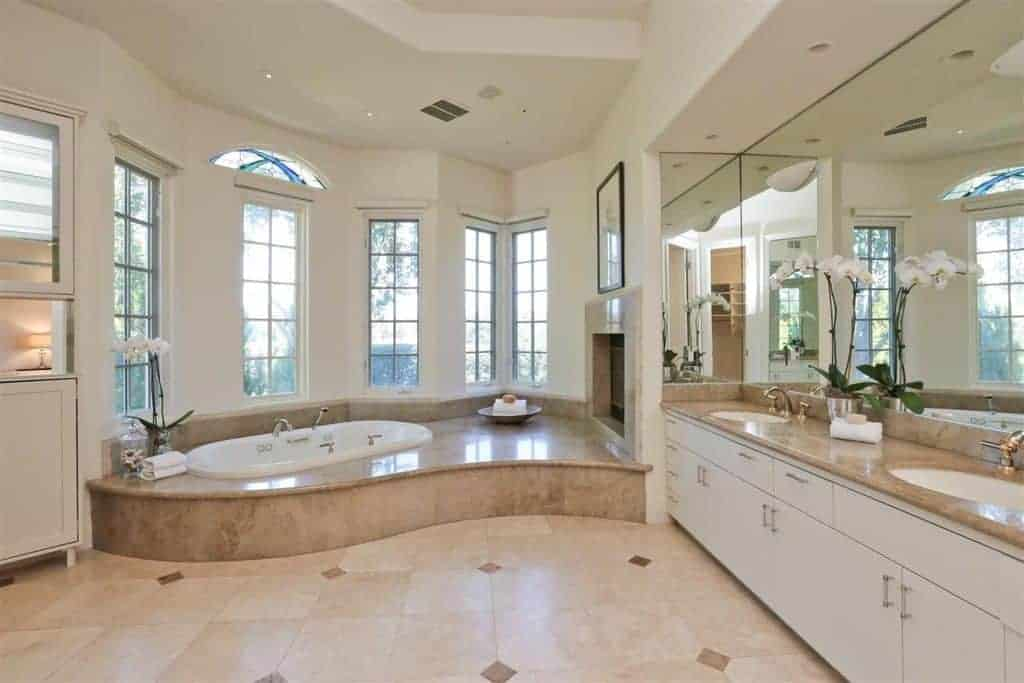The beige tiles of the flooring is reflected by the tiles housing the bathtub by the row of windows and the countertop of the two-sink vanity with white cabinets and drawers.
