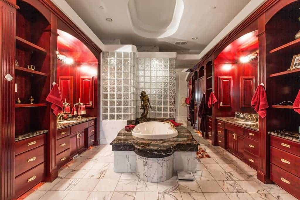 There is a brass figurine of a mermaid by the head of the bathtub in the middle of the white marble flooring in between two red wooden structures that house the vanities with the same dark marble countertop as the bathtub.