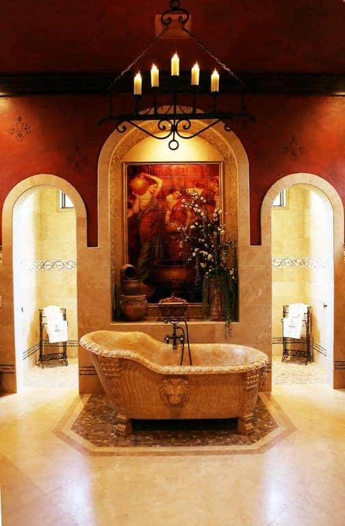 The highlight of this dramatic bathroom is the elegant freestanding bathtub with a carving of a lion head on the side. This is adorned with a wall of artworks and a wrought iron hanging candelabra above.