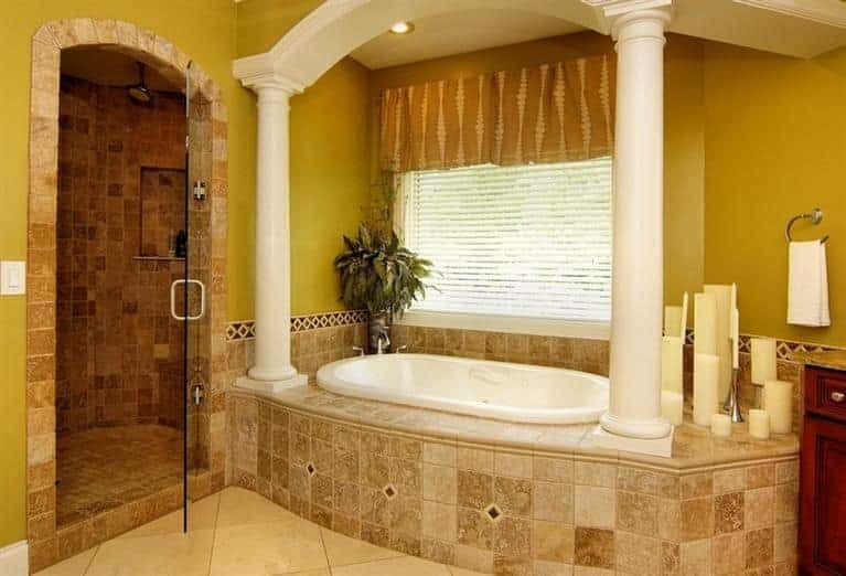 The beige tiles of the shower area extends to the housing of the bathtub that is flanked with dramatic white columns against yellow walls with a window above the bathtub.