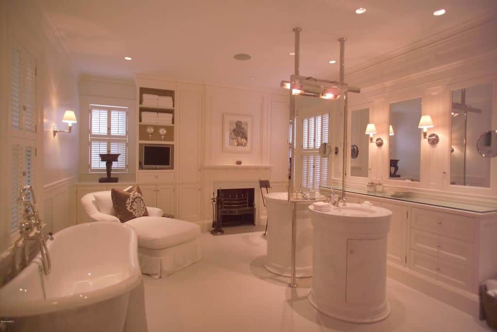 This white elegant bathroom, that looks more like a bedroom than a bathroom, has a white freestanding bathtub and a fireplace by the pair of sink areas in the middle of the white flooring.