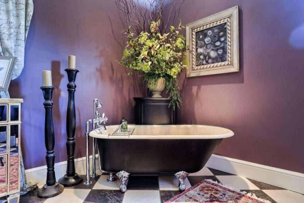 The black and white checkered flooring is complemented by the black and white freestanding bathtub that has silver legs. These are all given a background of purple walls adorned with a flower vase.
