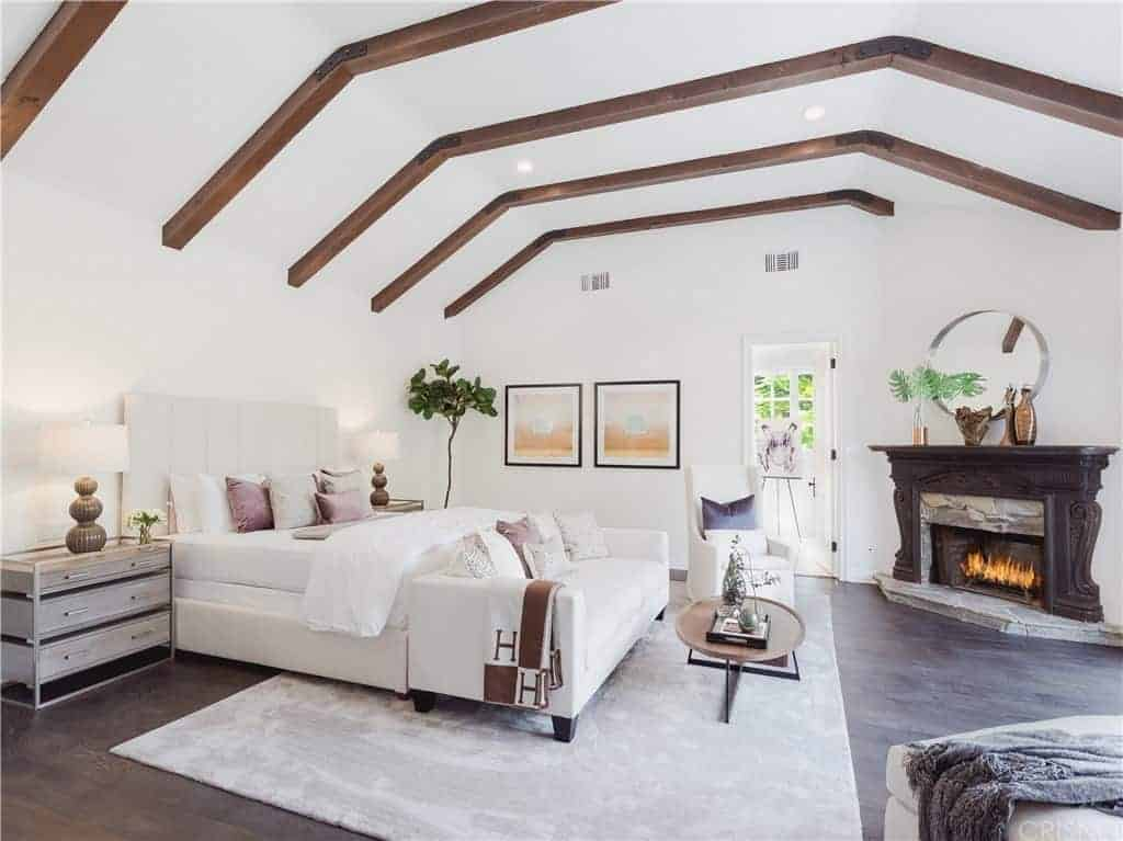 This lovely white master bedroom has a white bed with a cove ceiling has exposed wooden beams that follow the lay of the cove ceiling. The carved wood mantle of the fireplace stands out against the white walls.