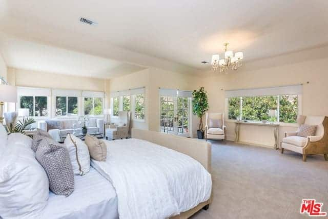 This spacious master bedroom has beige walls that partner well with the light gray carpeted flooring and the beige traditional bed. There are lots of sitting area by the windows that surround the room.