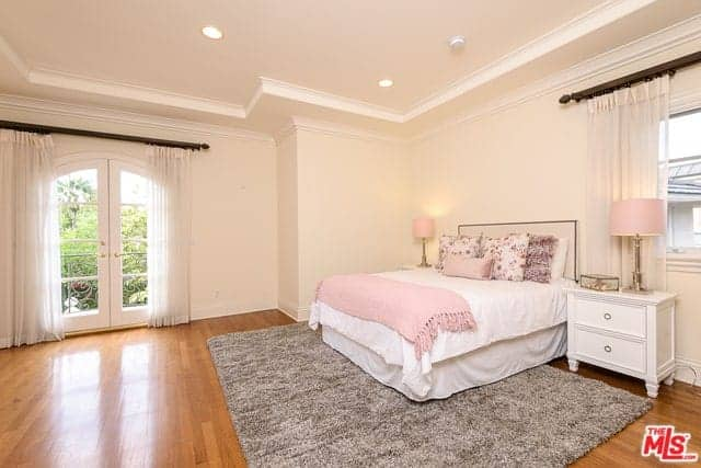 The pink walls and pink tray ceiling are complemented by the white bed and its white bedside drawers that has golden table lamps with pink cowls.