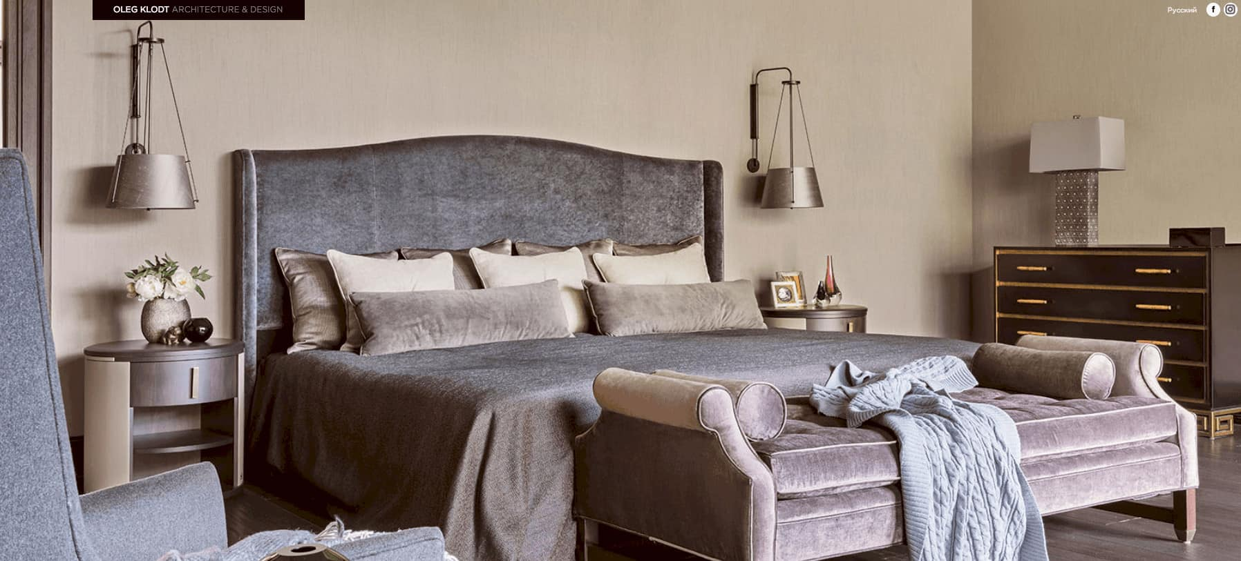 The gray velvet bed is paired with a gray velvet bench at the foot of the bed. This hue is also reflected on the bedside tables and the wall-mounted lights. This is given a nice background of beige walls and hardwood flooring.