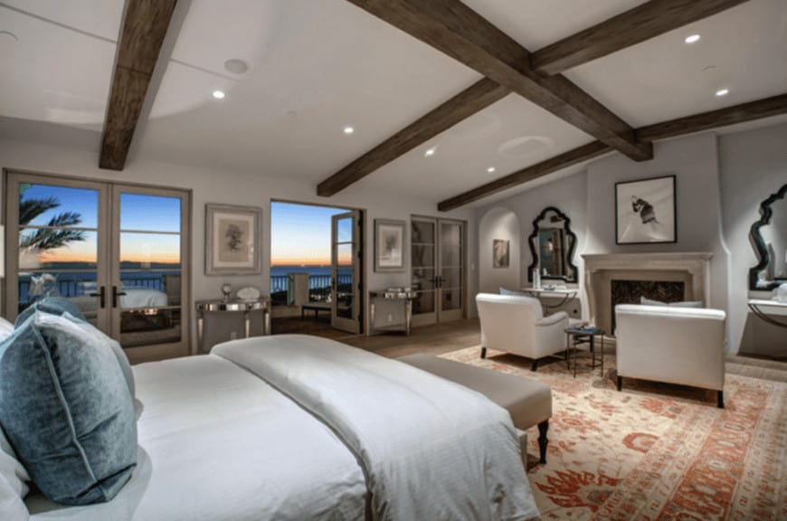 The tall shed ceiling has massive exposed wooden beams that seem to dwarf the other elements of this spacious master bedroom that has a fireplace with a sitting area and red patterned area rug over the hardwood flooring.