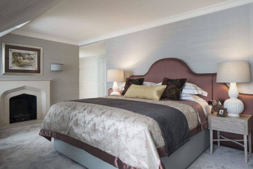 The traditional bed has a maroon cushioned headboard that extends to the wall behind the behind the bedside table and their white table lamps. The fireplace with a light gray mantle is a nice capstone to the overall aesthetic.