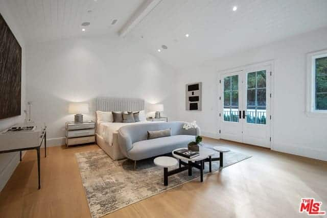 This airy and bright master bedroom has a high cathedral ceiling with a single exposed beam in the middle. This contrasts the hardwood flooring with an industrial area rug under the light gray couch by the foot of the light gray bed.