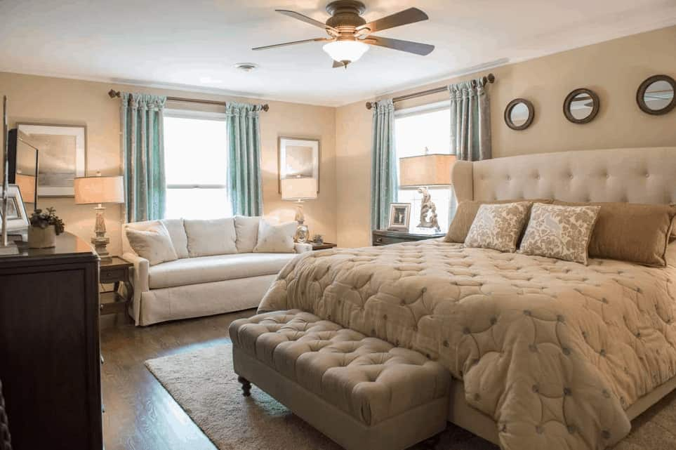 This master bedroom is dominated by beige walls, beige cushioned bed and the beige cushioned bench over the white area rug topping the hardwood flooring.
