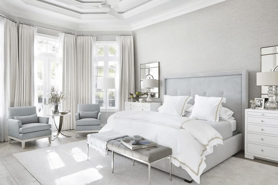 This airy master bedroom has subdued light gray hues that is brightened up by the tall white-framed windows that pair well with the white tray ceiling with a ceiling fan over the light gray bed with a cushioned headboard.