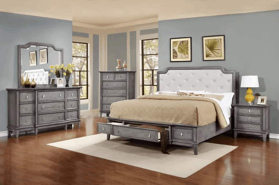 The light gray wooden bed has a customized feature of built-in drawers matching the bedside drawer and dressers complemented by a white area rug that contrasts the hardwood flooring.