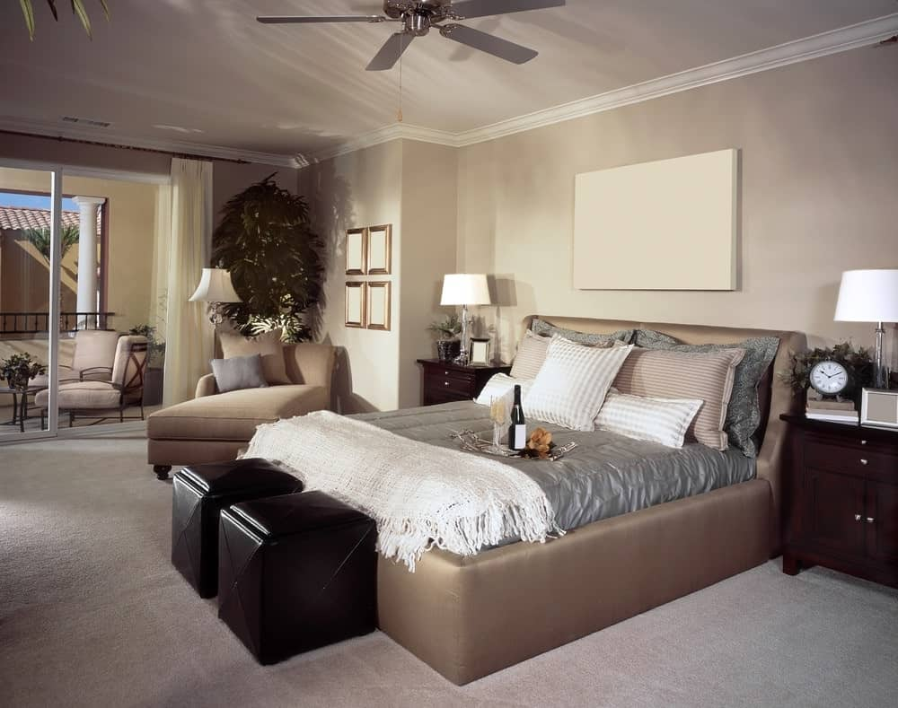 There is a blank white canvas hanging over the cushioned headboard of the traditional bed that stands out against the light gray carpeted flooring and its two bedside drawers and ottoman at the foot of the bed.