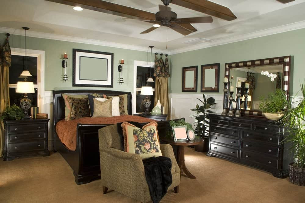 The light green walls of this master bedroom makes the dark wooden dresser stand out as well as the sleigh bed and the bedside drawers on each side of it.