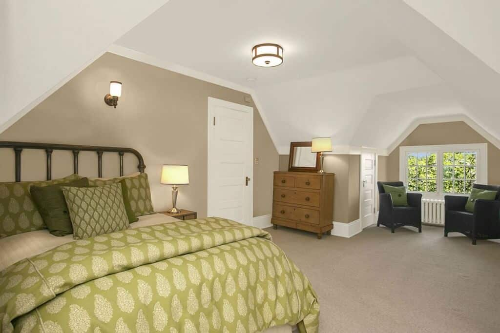 The green sheets and pillows of the traditional bed stands out against the beige carpeted flooring and beige walls paired with a white irregular vaulted ceiling.