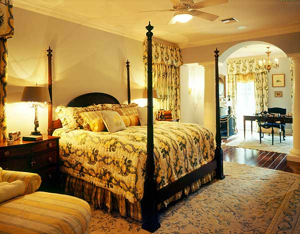 Chic floral patterns on the area rug, bedsheets and curtains provide a nice foreground for the hardwood flooring, dark wooden pencil poster bed and its wooden bedside drawers.