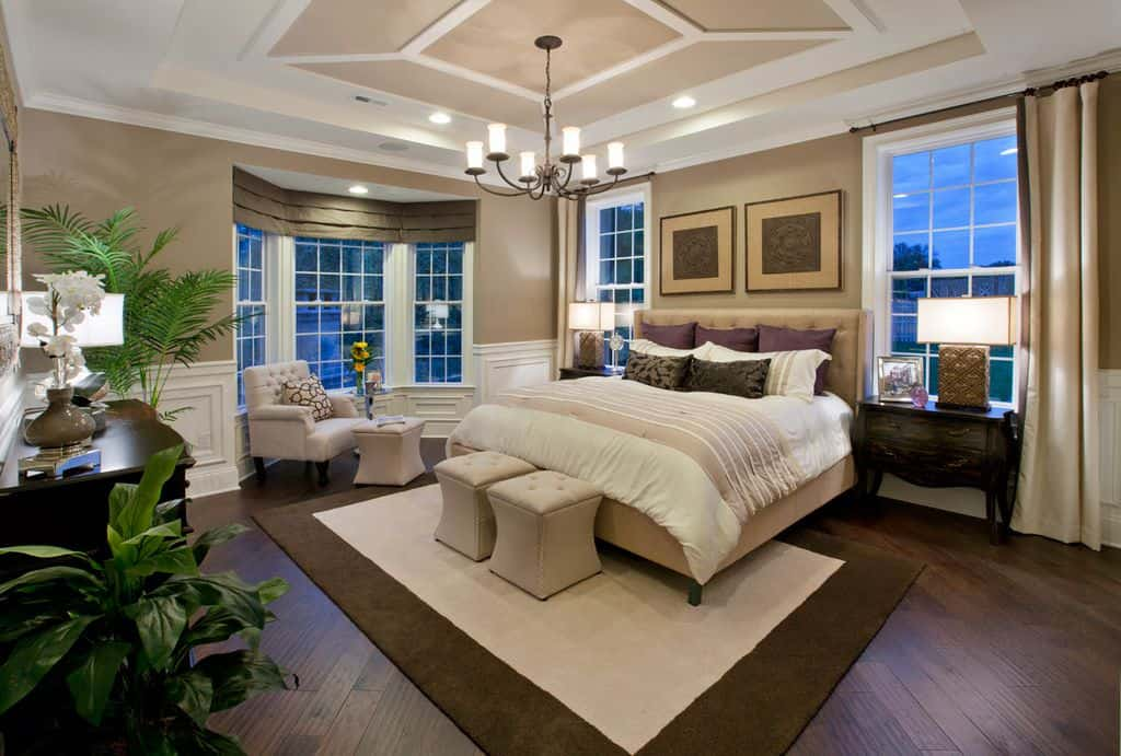 The dark hardwood flooring is topped with a white and brown area rug that complements the beige cushioned bed and its matching ottomans at the foot of the bed.