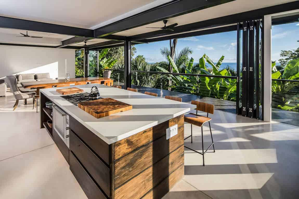 This Tropical-style kitchen is part of a great room that also houses the dining area and the living room all under its off-white ceiling with dark gray exposed metal beams matching the sets of folding glass doors that open up to an amazing tropical scene that works well with the wooden cabinetry of the kitchen island.