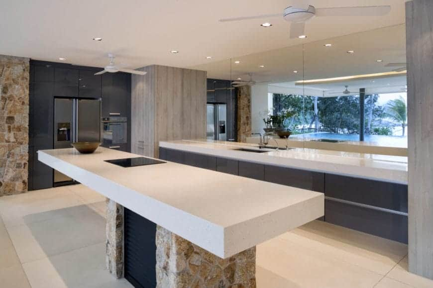 This sleek Tropical-style kitchen has white countertops for the dark gray kitchen peninsula as well as the kitchen island that has a textured rock support below matching the wall beside the dark gray structure that houses the modern fridge.