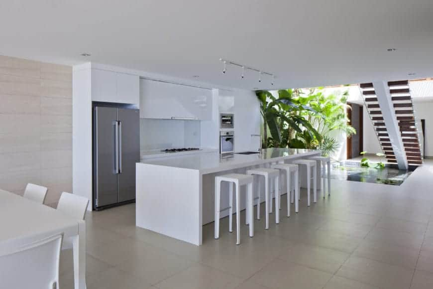 This kitchen is predominantly white with its white ceiling, white waterfall kitchen island, white peninsula as well as white stools for the breakfast bar. This white element of the kitchen is augmented by the miniature tropical garden beside it right below the stairs.