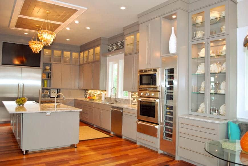 The light gray cabinetry of the peninsula and kitchen island works well with the stainless steel appliances and the off white countertops. These are contrasted by the redwood flooring augmented with yellow lights of the two small decorative chandeliers.