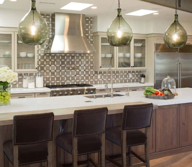 The beautiful and charming green glass hoods of the pendant lights stand out in this Tropical-style kitchen that has simple white countertops paired with a light gray patterned backsplash. These are all illuminated by the skylights of the white ceiling.