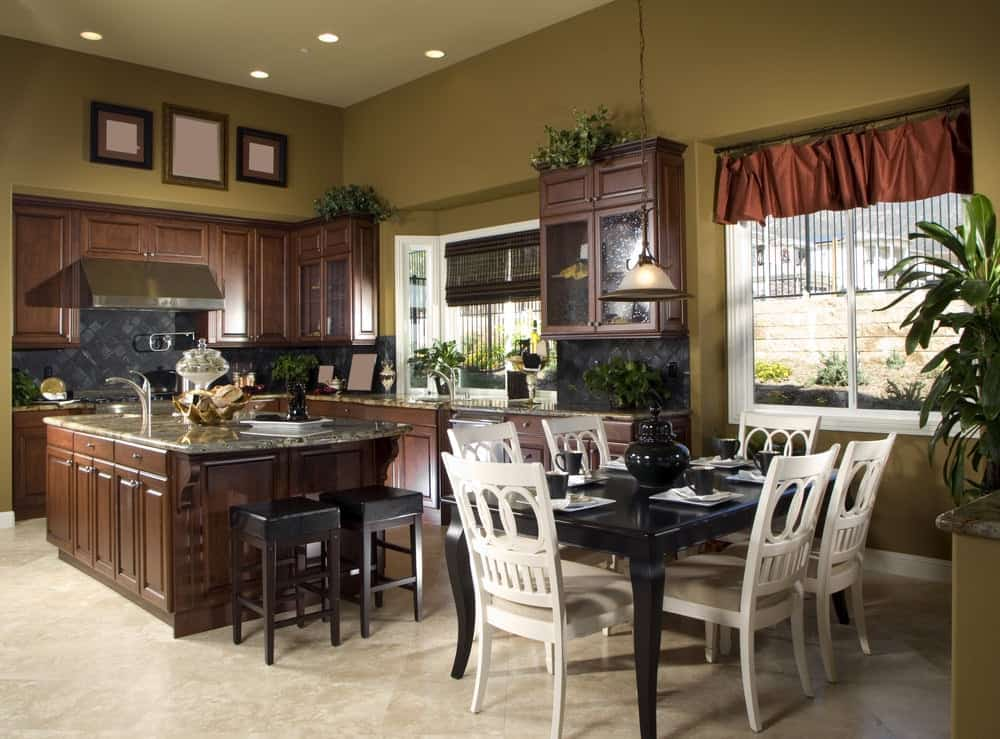 The relaxing olive green tone of the walls match well with the dark brown shaker cabinets and drawers of the island and peninsula. These are then complemented by the black backsplash tiles and that is augmented by the green plants.