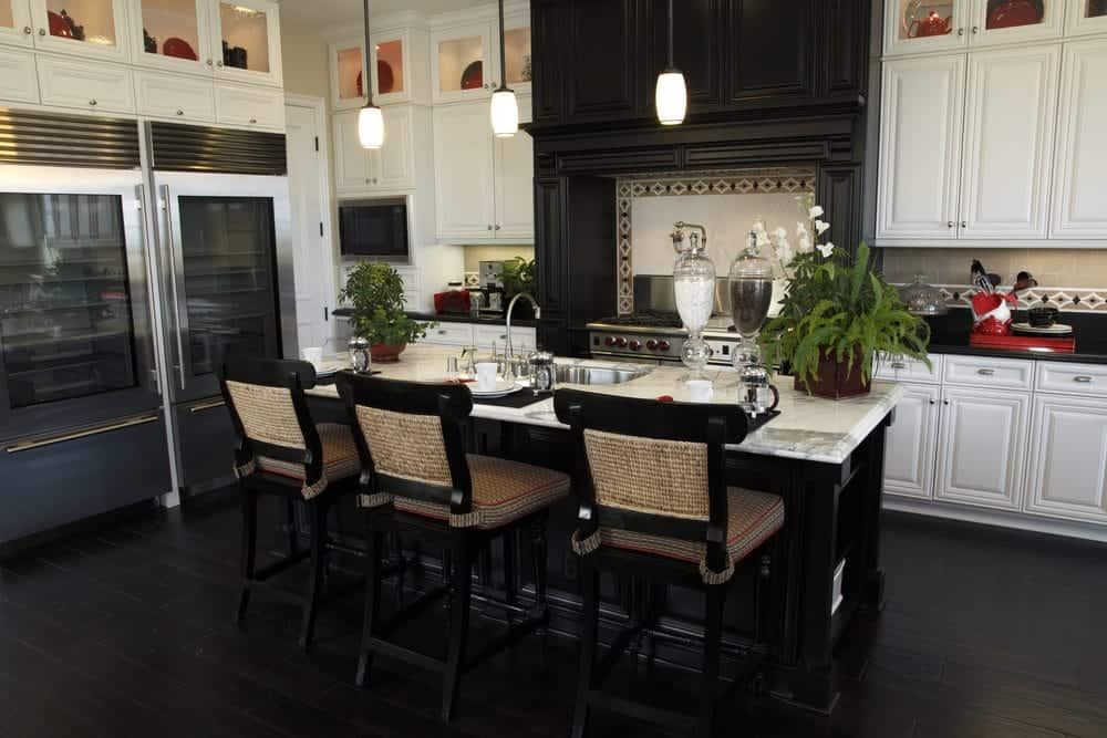 This Tropical-style kitchen has black hardwood flooring that blends with the black wooden kitchen island and the large wooden structure that houses the stove-top oven and its vent. This is flanked by the contrasting white cabinetry of the peninsula that has glass panels on top for the decorative dishware.
