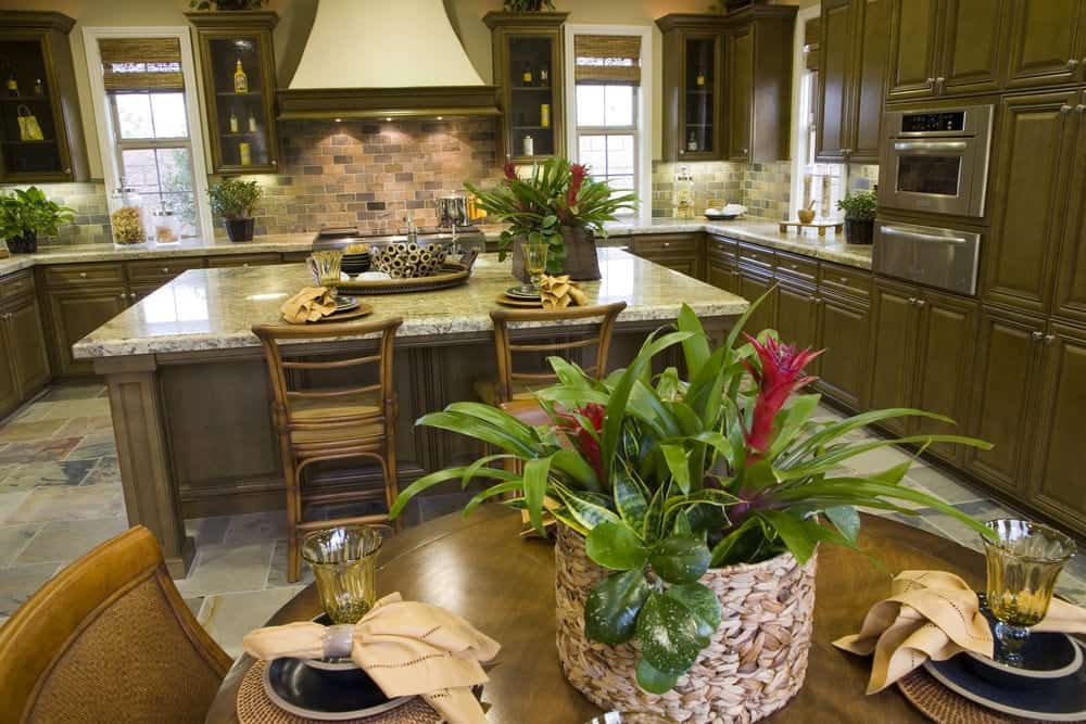 The U-shaped peninsula of the Tropical-style kitchen green wooden cabinets and drawers that matches the various potted plants that adorn the marble countertops. These are then paired with brick backsplash that are lit by the lights underneath the floating cabinets.